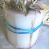 White candle with herbs on top